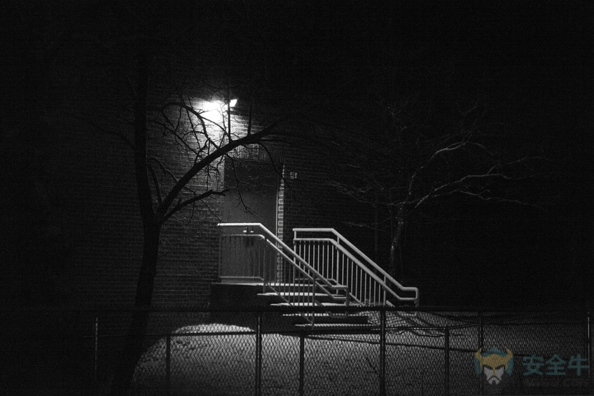 Illuminated back door and stairs in the dark of night.